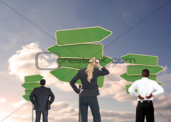 Group of businesspeople looking at empty signposts