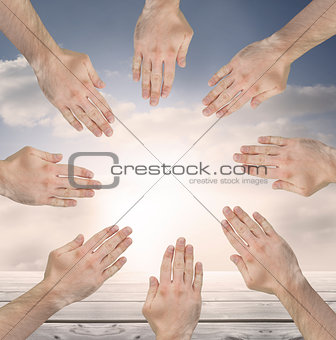Group of hands forming a circle over blue sky