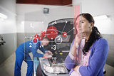Auto mechanic with customer looking at futuristic interface