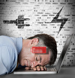 Businessman sleeping on his laptop with low energy and charging symbols