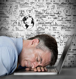 Businessman sleeping on his laptop with drawings and charts