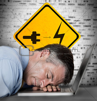 Businessman sleeping on his laptop with battery plug roadsign