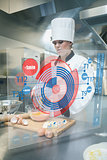 Pastry chef making dough while consulting futuristic interface