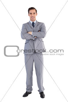Smiling businessman standing with his arms crossed