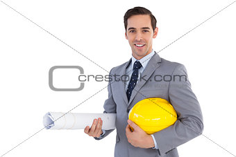 Smiling architect holding plans and hard hat