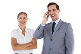 Smiling businessman on the phone next to his colleague