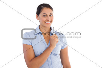 Thoughtful smiling businesswoman holding a pen