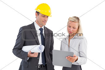 Architects with hard and plans looking at clipboard
