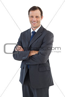 Charismatic smiling businessman standing with arms crossed