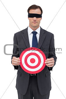 Blindfolded businessman holding a red target
