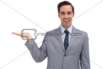 Smiling businessman presenting something with his hand