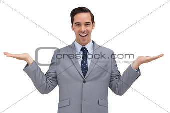 Smiling businessman presenting something with his hands