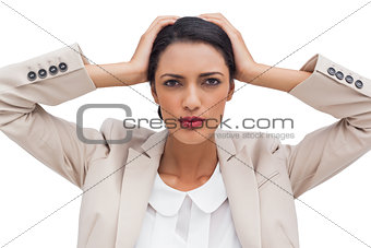 Stressed businesswoman holding her head between hands