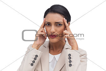 Young businesswoman putting her fingers on her temples