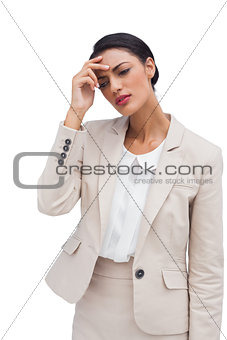 Worried young businesswoman holding her head