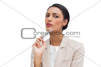 Thoughtful young businesswoman holding a pen