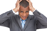 Exhausted businessman holding his head between hands