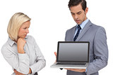 Businesswoman looking at laptop held by her colleague