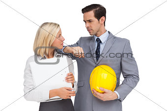 Architects with plans and hard hat looking at each other