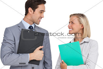 Smiling business people looking at each other with folders