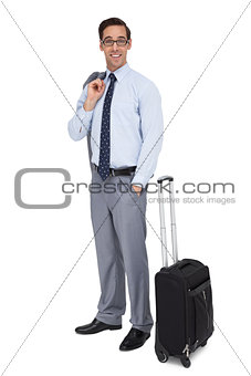 Smiling businessman standing next to his luggage