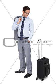 Smiling businessman looking at his suitcase