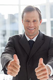 Smiling confident businessman giving thumbs up