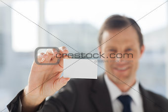 Smiling businessman showing business card