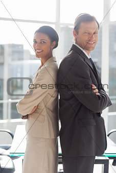 Smiling business people standing back to back
