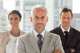 Businessman standing with colleagues behind
