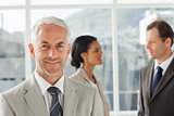 Confident businessman standing in front of colleagues speaking together