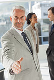 Businessman giving a handshake with colleagues behind