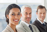 Cheerful businesswoman smiling with colleagues behind