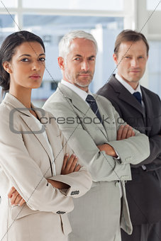 Three serious business people standing together