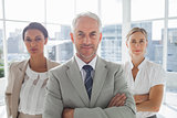 Confident businessman standing in front of colleagues