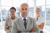 Serious businessman standing in front of colleagues