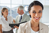 Cheerful businesswoman in front of colleagues working behind