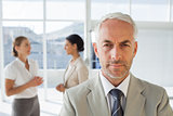 Serious businessman standing while colleague are discussing together