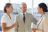 Likeable businessman speaking with female colleagues