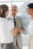 Mature businessman discussing with female colleagues