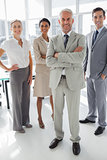 Cheerful businessman standing in front of colleagues