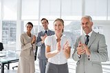 Group of business people applauding together