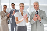 Smiling business people applauding together