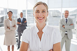 Cheerful businesswoman standing with arms folded