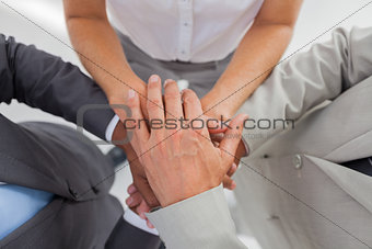 Business people gathering their hands together