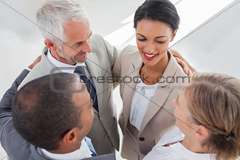 Smiling business people embracing together