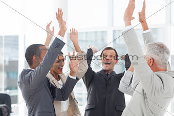 Group of smiling business people raising their hands