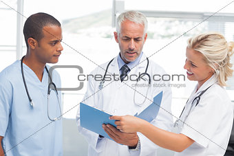 Three serious doctors examining a file