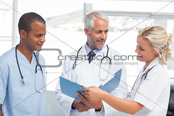 Three smiling doctors examining a file