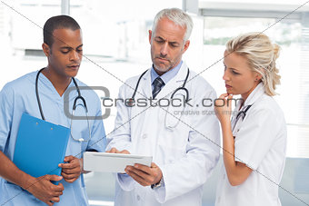 Three doctors using a tablet